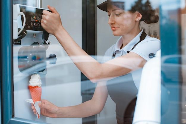 여성 판매자가 손에 자판기에서 꼬인 아이스크림이 든 콘을 들고 있습니다. 소상공인 및 테이크아웃 음식, 여름 음식, 더위 식히기