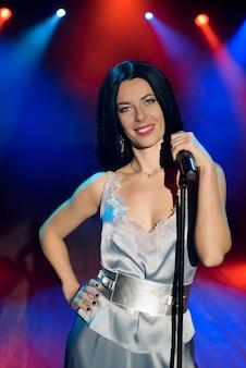 Певица, держащая микрофон против красочных огней сцены. яркий фон с неоновыми огнями.