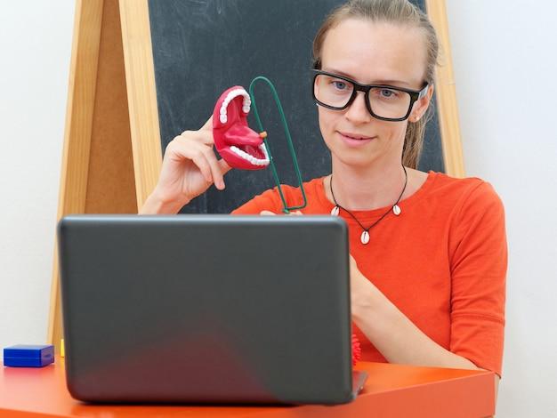 Женский логопед проводит онлайн-урок с ноутбуком.
