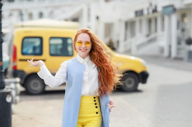明るく長い黄色の髪を持つ女子学生が街を歩く