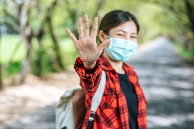 배낭을 들고 도로에서 금지하는 다섯 손가락을 올리는 여성 관광객.