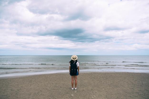 배낭과 모자를 들고 바닷가 해변에 혼자 서 있는 여성 여행자