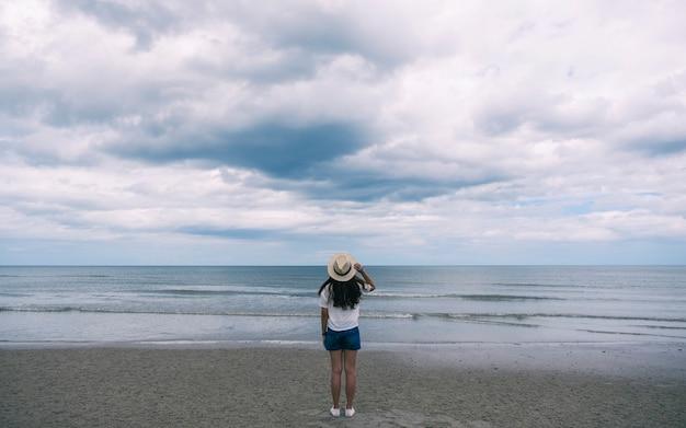 바다 해변에 혼자 서 있는 모자를 쓴 여성 여행자