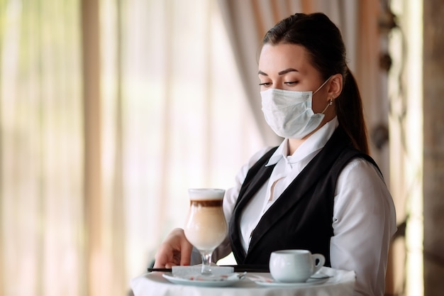 의료 마스크에 유럽 모양의 여성 웨이터가 라떼 커피를 제공합니다.