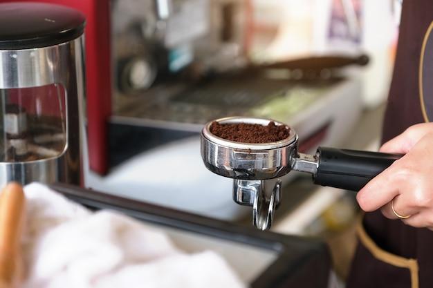 Работница прижимает молотые кофейные зерна к трамбовке.