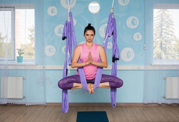 Учительница йоги сидит в фиолетовом гамаке в позе йоги