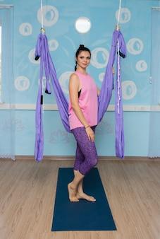 Йога в спортивном костюме стоит рядом с гамаком в студии