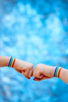 ぼやけた背景に虹色のリストバンドでハンドサインを作る女性