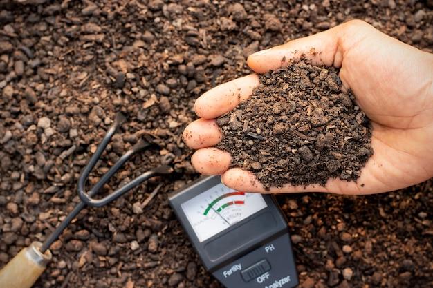 농부의 손에 있는 비옥한 양토와 제자리에 있는 토양 측정.