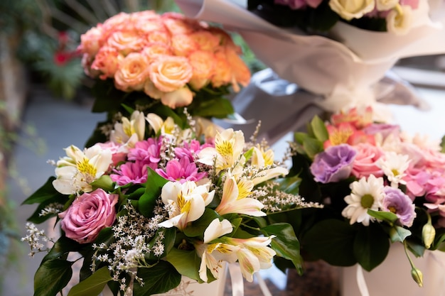 太陽の光の中でバラや他の夏の花のお祝いの花束。花の背景