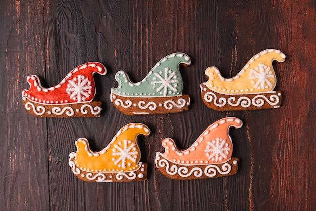 На деревянном коричневом фоне лежали праздничные рождественские и новогодние пряники в виде санок.