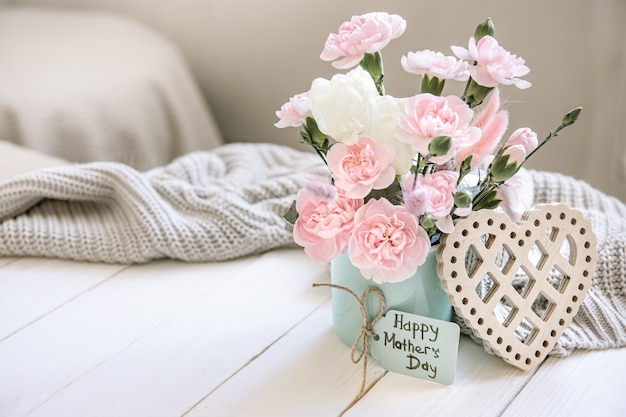 Праздничная композиция с живыми цветами в вазе, элементами декора и пожеланием счастливого дня матери на открытке.