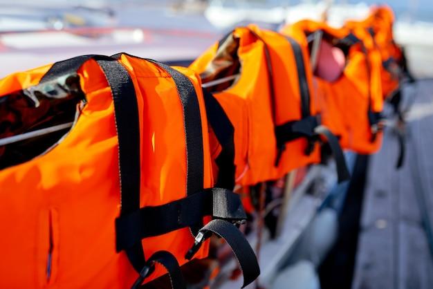 ヨットの柵にある明るいオレンジ色のライフジャケット。高品質の写真