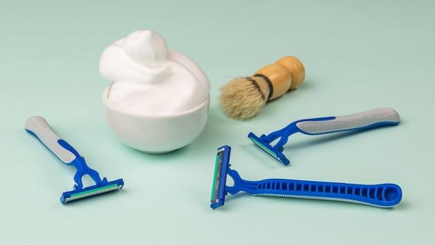 いくつかの使い捨てカミソリ、ブラシ、およびシェービングフォームのボウル。男性の顔のケアのために設定します。
