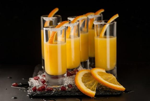 暗い背景の黒い石の上にオレンジ色の飲み物と氷を数杯