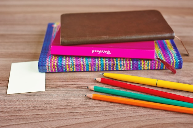 いくつかのメモ帳、木製のテーブルに鉛筆