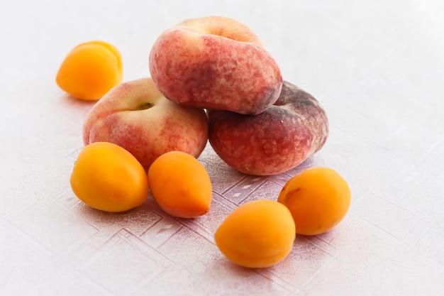 白いテーブルクロスの上にいくつかの桃とアプリコット