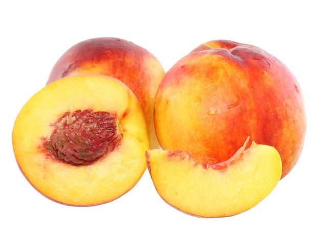白い背景の上に、1つのスライスを持ついくつかの桃。孤立
