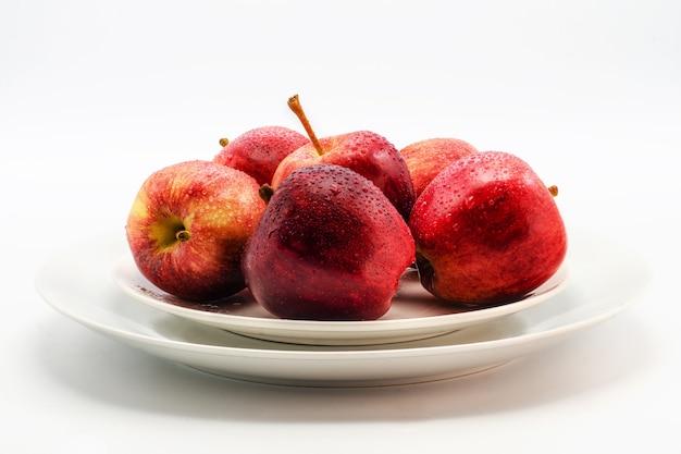 Несколько красных яблок, лежащих на белой тарелке на белом