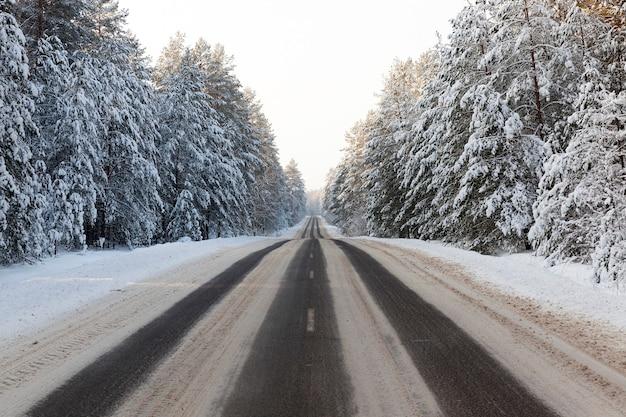 冬に通り過ぎる車からのアスファルト道路のいくつかのトラック、雪が溶けた