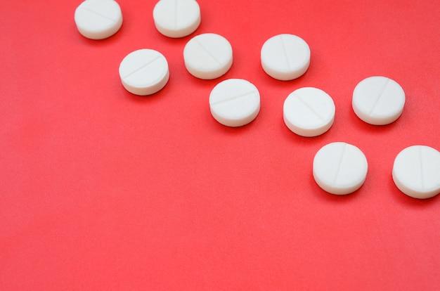 いくつかの白い錠剤は明るい赤の背景面にあります