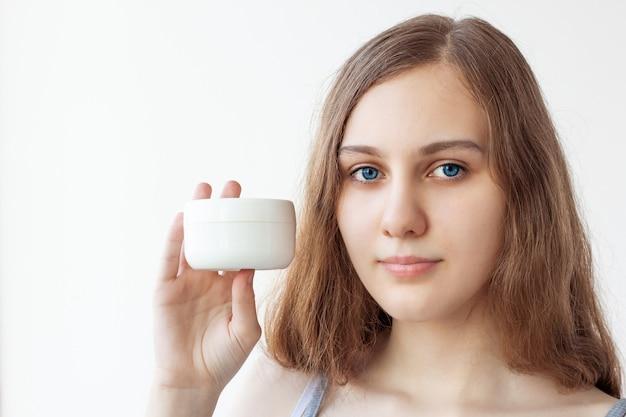 長い茶色の髪、青い目、透明な肌を持つ15歳の10代の少女は、白いクリームの瓶を手に持っています。セルフケア、スキンケア。スペースをコピーします。