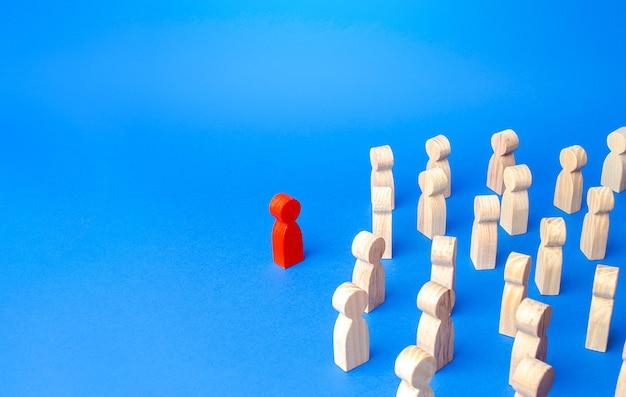 Фигурка красного человечка стоит в стороне от толпы людей. концепция лидерских качеств.