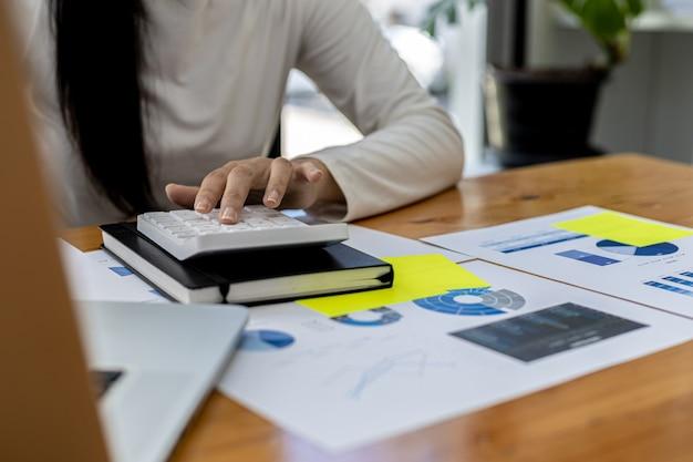 재무 직원은 노트북에서 회사 재무 데이터의 정확성을 확인하기 위해 계산기를 누르고 경영진과의 회의에 가져올 회사 재무 요약을 준비합니다.