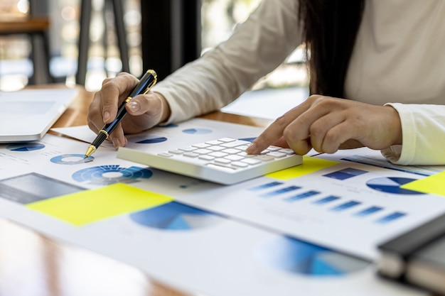 財務担当者は、会社の財務書類の情報の正確さを確認するために計算機を押し、経営陣との会議のために会社の財務概要を準備します。