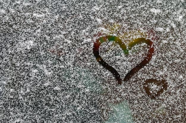 雪に覆われた車のフロントガラスに指で描かれたハート。 lgbt。バレンタインデーのコンセプト。バレンタインデーの創造的な背景。テキスト用のスペースをコピーします。