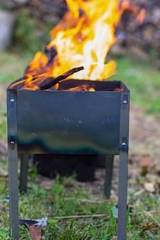 В металлической решетке горит огонь. большое яркое пламя огня с близкого расстояния. отдых на свежем воздухе. 3