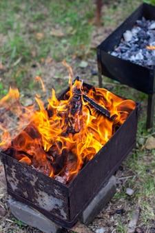 В металлической решетке горит огонь. большое яркое пламя огня с близкого расстояния. отдых на свежем воздухе. 6