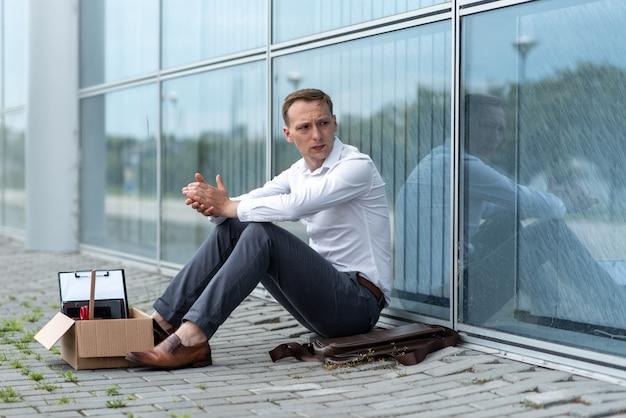 解雇されたサラリーマンが近代的なオフィスビルの近くの床に座っています。その男は解雇をとても心配している。男は目をそらして握手します。