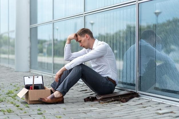 Уволенный офисный работник сидит на полу возле современного офисного здания. мужчина очень переживает за увольнение.
