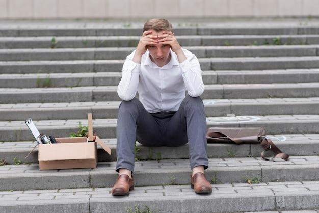 解雇されたサラリーマンが階段に座っています。その男は次に何をすべきか分かりません。その隣には文房具の入った段ボール箱があります。