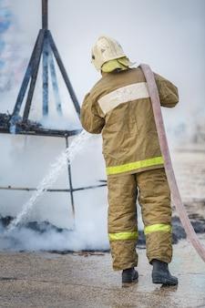 消防士が煙の中に残った火を消す