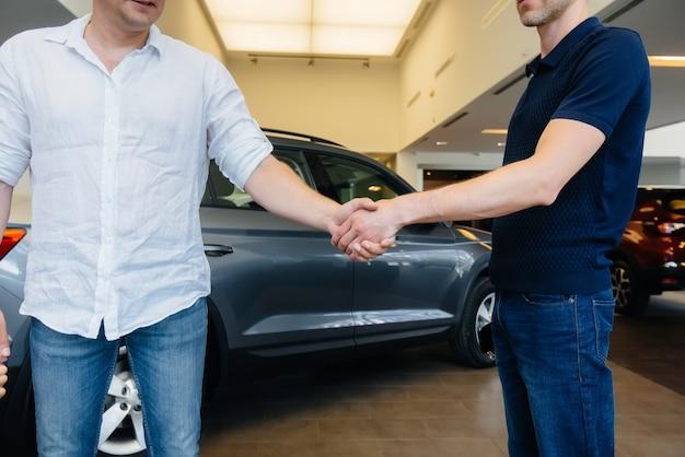 若いファミリーカー販売店で新車を購入した後のしっかりとした握手。車の販売。