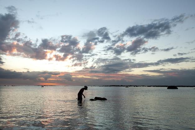 Рыбак ловит рыбу в океане на закате.