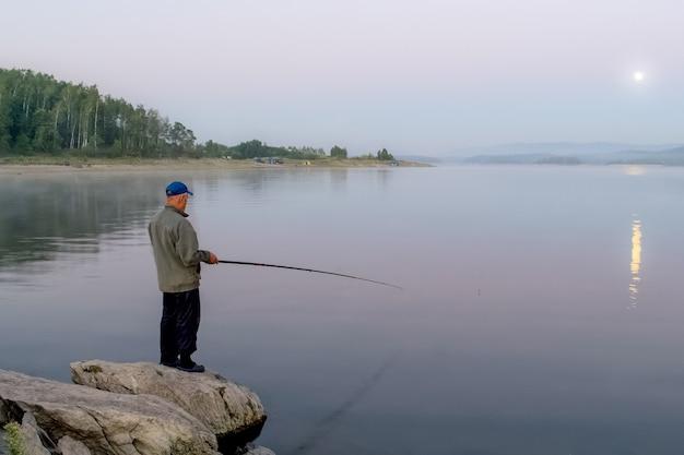 Рыбак ловит рыбу рано утром на озере луна светит в небе