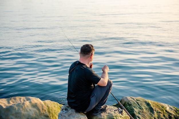 Рыбак ловит рыбу в море удочкой, сидя на берегу скал на закате