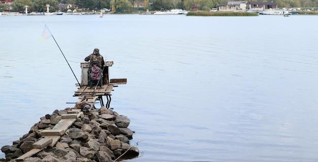 어부는 은행에서 강, 후면보기에서 물고기를 잡는다. 어부는 강둑의 나무와 돌 다리에 앉아 물고기를 잡으려고 합니다. 스포츠, 레크리에이션, 라이프 스타일.