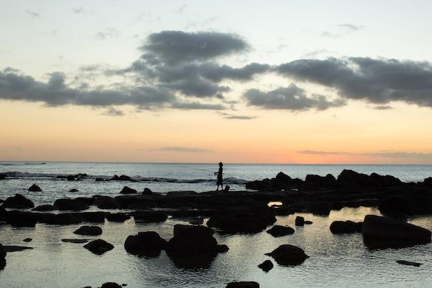 漁師が海の黒い石で釣りをしています。