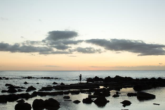 Рыбак ловит рыбу на черных камнях в океане.