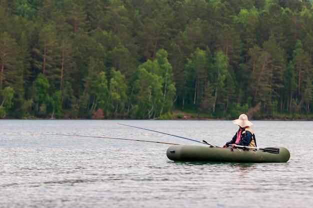Рыбак ловит рыбу на удочки с резиновой лодки веслами. у рыбака большая шляпа от солнца. две удочки. выборочный фокус. деревья на размытом фоне.
