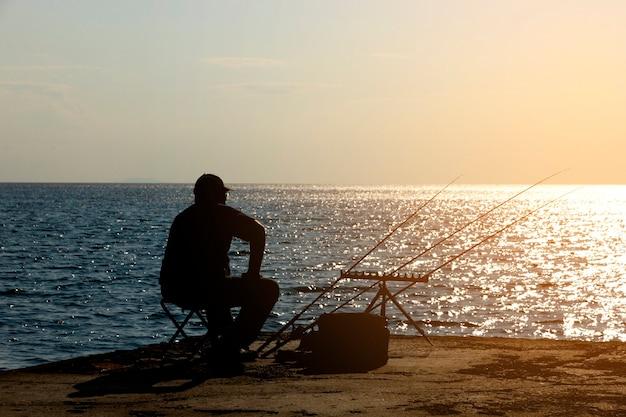 Рыбак ловит рыбу удочкой на берегу моря напротив солнца. фото высокого качества