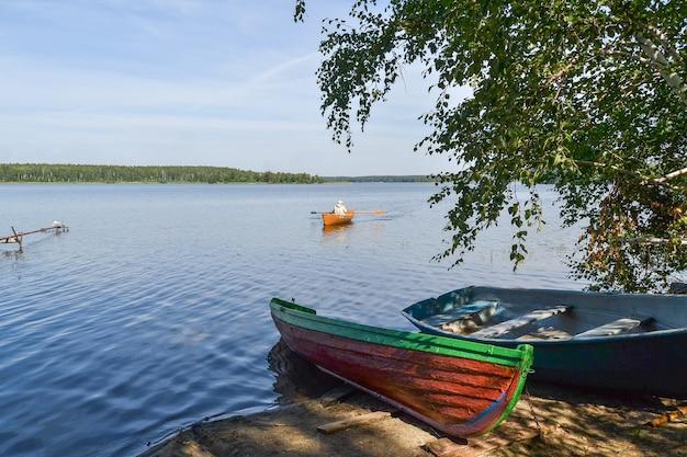 Рыбак плывет на лодке по озеру к берегу