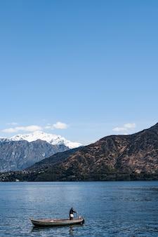Рыбак на лодке у побережья на фоне гор на озере комо в италии.