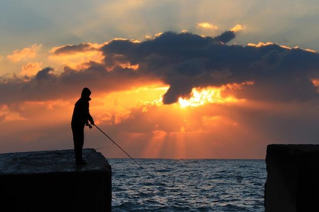 Рыбак на скале против неба рассвета