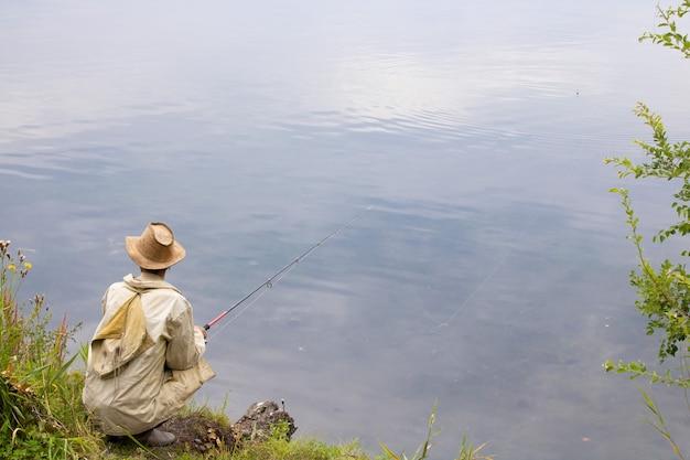 호숫가에 있는 한 어부가 낚싯대로 낚시를 하고 있다