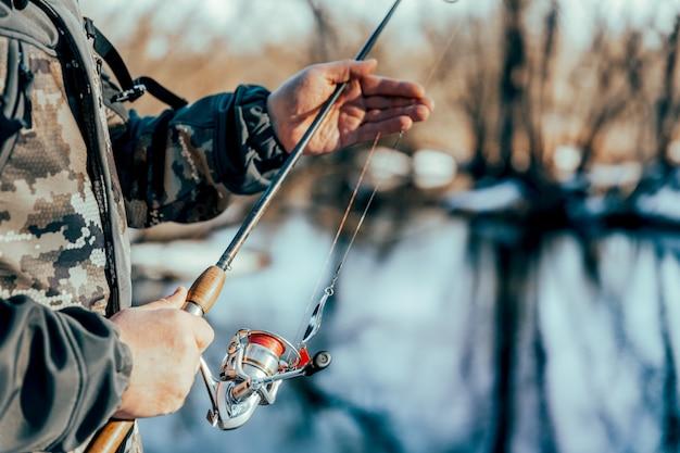 Рыбак с удочкой ловит рыбу на берегу заснеженной реки ранней весной.